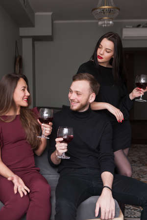 Female jealousy on party. Possessive relationship. Dissolute smiling male at party, distrust in company. Communication with wine, love triangle