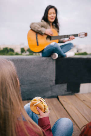junkie: Music junkie with junk food on live show. Girl with fastfood in hands listen singers acoustic guitar improvisation.