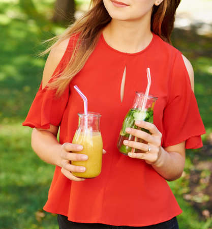 Healthy lifestyle. Unrecognizable young woman with fruit detox smoothie in summer, on green nature background. Diet, well being and weight loss concept Stock Photo