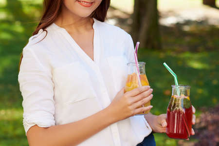 Healthy lifestyle. Cute young woman with fruit detox smoothie in summer, on green nature background. Diet, well being and weight loss concept