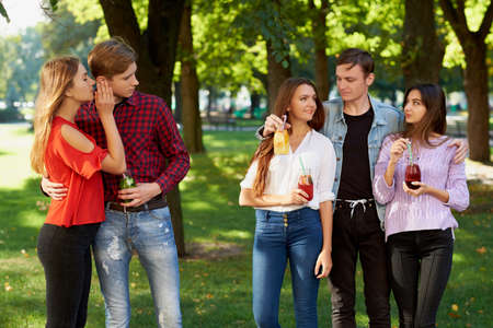 Jealousy and envy in friends relationship. Cheerful young people with detox cocktail having outdoor summer party Stock Photo