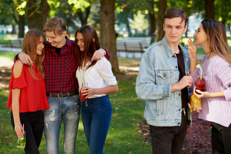unfaithful: Jealousy and envy in friends relationship. Cheerful young people with detox cocktail having outdoor summer party Stock Photo