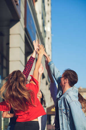 Happy young friends teamwork. Group of man amd woman with hands together doing give high five gesture. Friendship forever, togetherness, youth team , success concept Stock Photo