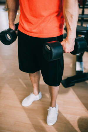 Dumbbells training workout man gym concept. Hard work on your body. Bodybuilding culture. Stock Photo