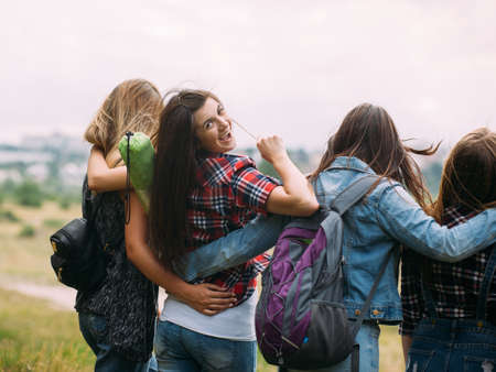 Friendly hugs admire nature tourism concept. Travelers group unity. Smiling girl look back.