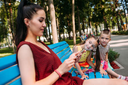 Children try to attract mothers attention at park. Business hinders spending time with family. Stock Photo