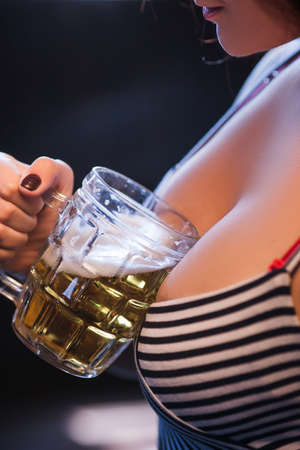 Woman with big breasts holding a glass of beer. Every mans dream girlfriend concept