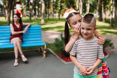 Children secrets behind mother back at park. Gossip for a walk. Stock Photo