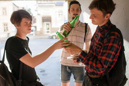 Geek boy falls under bad influence. teenage alcohol addiction bad habits concept. Modern urban youth lifestyle 版權商用圖片