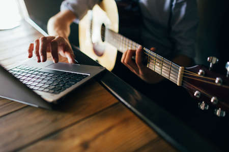 online music courses. young man learns how to play guitar through the internet. modern technology education benefits concept