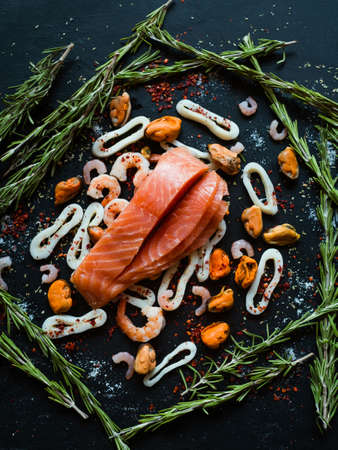 Seafood and salmon assortment on dark background. Omega 3 acid unsaturated fats. Healthy eating. Mediterranean cuisine concept