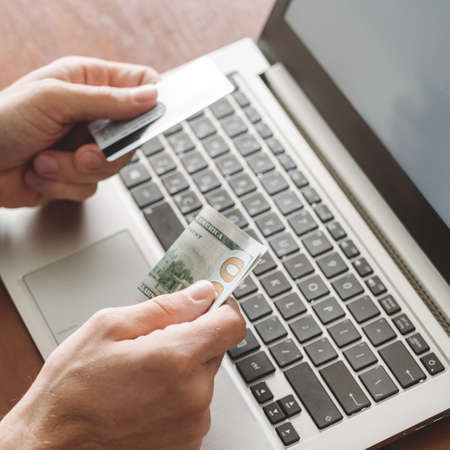 Online gambling. Man holding credit card and money reapy to play at internet casino on his laptop. Luck success and winning concept Stock Photo