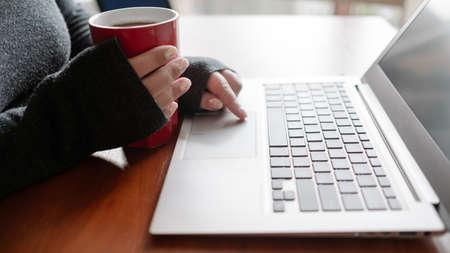 Donna che mangia un tè e abbuffata guardando le sue serie TV preferite sul computer portatile. Download di film e streaming video