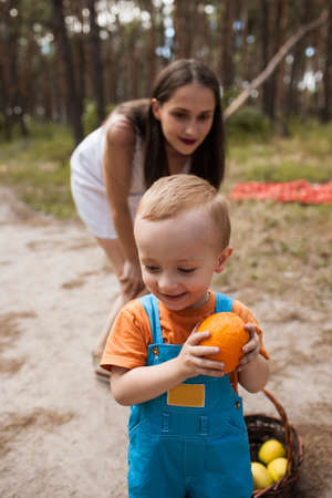 Child hide orange family picnic concept. Little cunning. Healthy lifestyle. Happy motherhood.