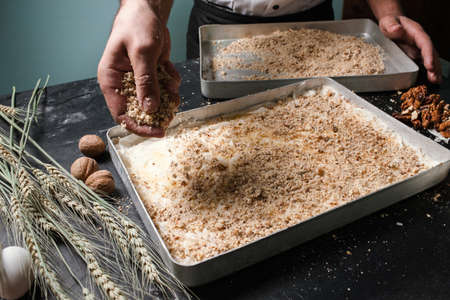 Food pastry dessert recipe concept. Chef making  baklava with nuts at restaurant.