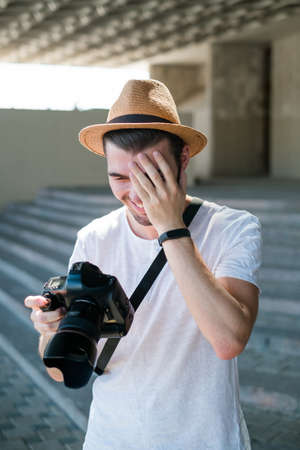 photography fails. professional photographer laughs at some bad shot. stupid accidental mistakes. working process concept