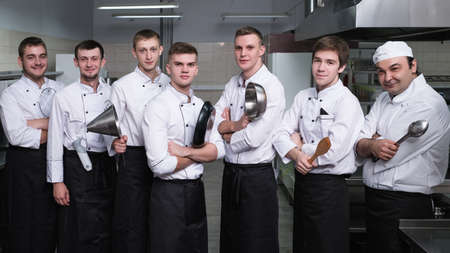 Casting process to find the best for a cooking competition. Male cooks stand confident with kitchen utensils in their arms. Dream of being a chef comes true 写真素材