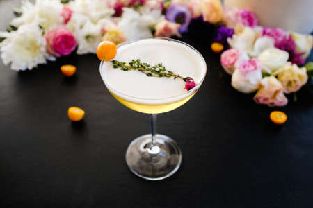 ladies mimosa alcoholic cocktail recipe concept. delicious beverages. floral decoration on dark background. Stock Photo