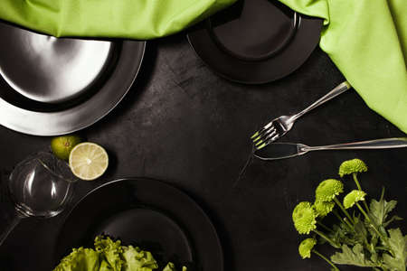 Plates and cutlery on black background with contrast green color. Creative fancy restaurant table setting. Art and design concept