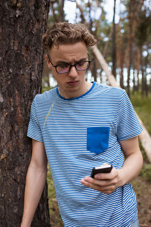 Self-confident man look at his own phone in the forest. Alone with problems. Dependence on gadgets