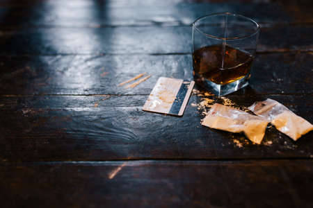 Cocaine and alcohol drink on dark background. Detrimental lifestyle. Bad habits. Alcohol and drug addiction. Important problem of modern society Stok Fotoğraf