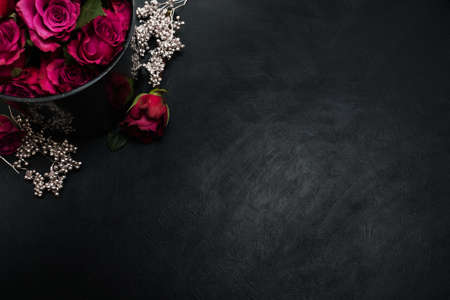 Burgundy or wine red roses and silver decor on dark background.