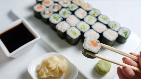 homemade sushi assortment. Asian cuisine and Japanese food concept. Woman tasting rolls with chopsticks Stock Photo
