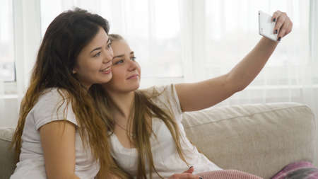 selfie using smartphone. friends idle pastime lifestyle. young girls taking photo at home