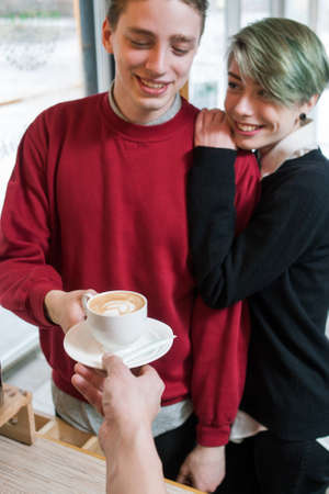 young hipster couple buying coffee at cafe. youth lifestyle and leisure concept.