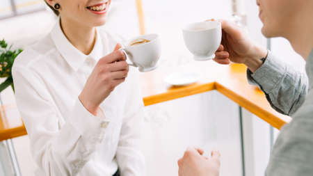 communication. couple of coworkers or friends having a pleasant conversation while drinking coffee in a cafe. joyful talk