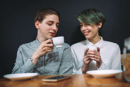 friends communication and leisure. bff drinking coffee in a bar talking and smiling. pleasant conversation between young man and woman