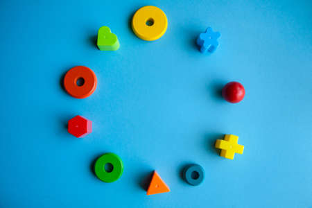 child creativity art and handcraft. construction kits for fine motor skills development. colorful wooden pieces or plastic details in a circle on blue background.