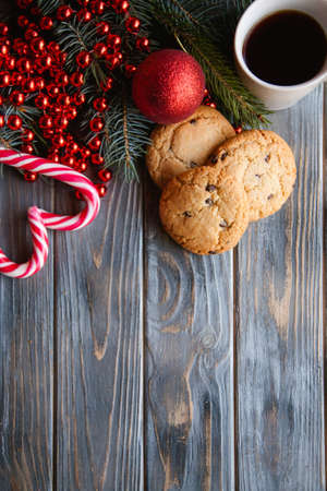 holiday seasonal decoration on wooden background. chocolate chip cookies and candy canes in heart shape. christmas foods concept.