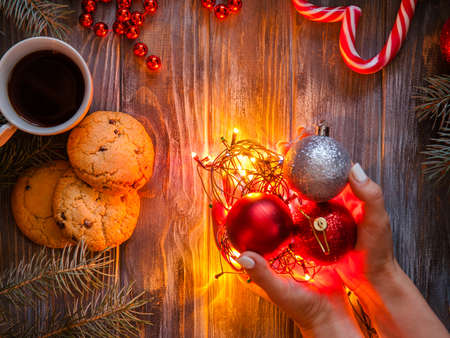 cozy warm holiday decor on wooden background. christmas spirit and festive mood created woman hands holding fairy lights and shiny balls. cup of coffee chocolate chip cookies and candy cane.
