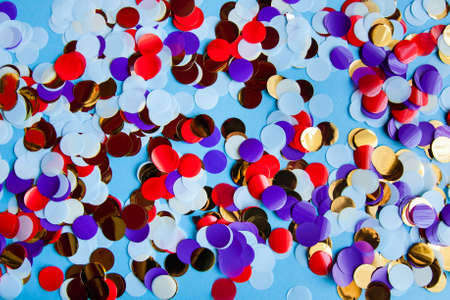 assortment of multicolored shiny confetti on blue background. new year celebration and festive holiday concept.