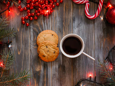 cup of coffee and a chocolate chip cookie surrounded by festive winter holiday decor. christmas spirit and leisure concept.