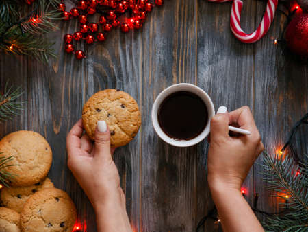 christmas holidays and leisure during festive season. woman hand holding a cup of coffee and a chocolate chip cookie. warmth coziness and snacking concept.