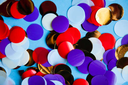 colorful mix of circular confetti on blue background. festive celebration and fun concept. abstract glossy backdrop.
