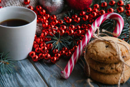 cozy warm holiday decor on wooden background. christmas spirit and festive mood. knitted sweater and red bead string with a cup of hot coffee and chocolate chip cookies.