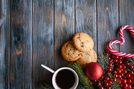 cup of coffee and chocolate chip cookie surrounded by festive winter holiday decor. christmas spirit and leisure concept. red bead string ball fir tree branch and candy cane mix.
