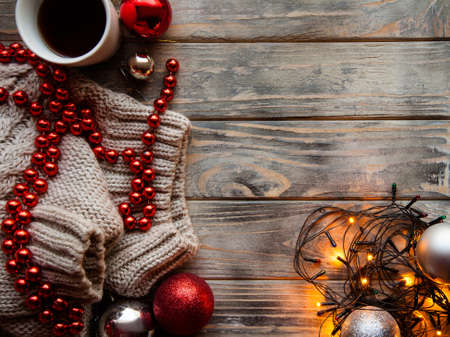 cozy warm holiday decor on wooden background. christmas spirit and festive mood. fairy lights knitted sweater and red bead string with a cup of hot coffee.