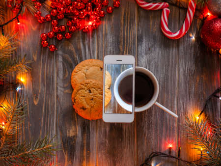 blogging and mobile photography concept. christmas and new year festive decor on wooden background, fairy lights and bead strings surrounding cup of coffee and chocolate chip cookies. Stock Photo