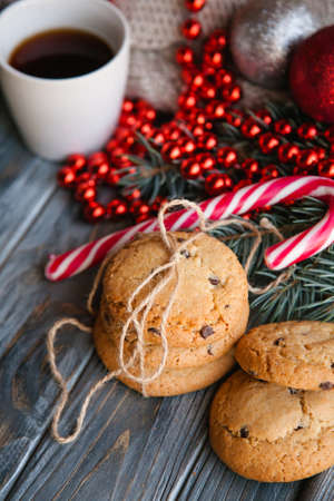 holiday cooking and pastry. christmas food snacks concept. sweet delicious chocolate chip cookies in the festive new year decor of candy cane and red bead string. Stock Photo
