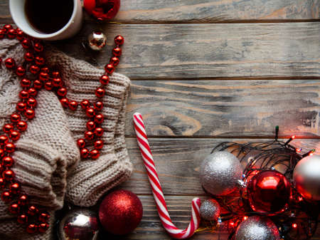 christmas spirit and holidays festivity. assortment of decor elements on wooden background. fairy lights knitted sweater red bead string and balls with a cup of hot coffee.