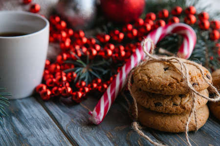 christmas festive food snack concept. pile of chocolate chip cookies and a mug of tea on wooden background. red bead string seasonal decoration in the backdrop.