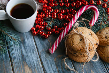 cup of coffee and chocolate chip cookie mixed with festive winter holiday decor. christmas spirit and leisure concept. red bead string on fir tree branch and candy cane. Stock Photo