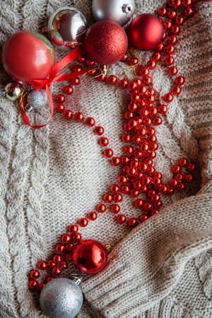 festive cozy christmassy atmosphere. holiday decorative baubles and red bead string on knitted sweater.