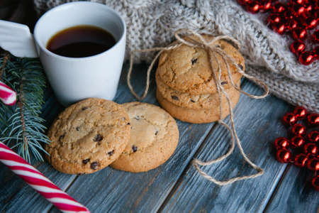 christmas holiday food snack concept. chocolate chip cookies and a mug of tea on wooden background. seasonal decoration.