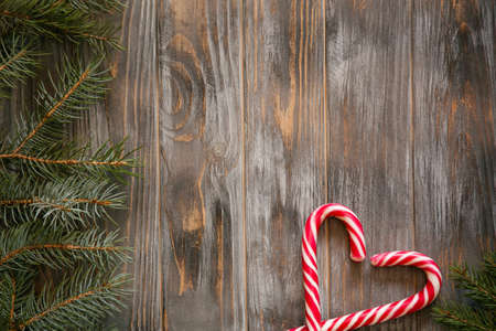 festive cozy christmassy atmosphere. minimalistic holiday decor. fir tree branch and candy cane in heart shape on wooden background.