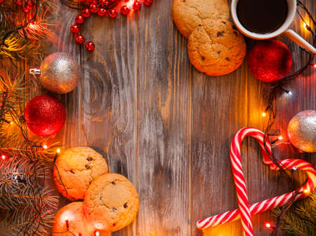 cozy warm holiday decor on wooden background. christmas spirit and festive mood created by fairy lights and shiny balls. cup of coffee chocolate chip cookies and candy cane in heart shape. Stock Photo